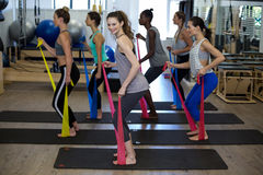 Fit women performing stretching exercise with resistance band Royalty Free Stock Images