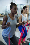 Fit women performing stretching exercise with resistance band Stock Photos