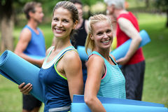 Fit women posing with sports mats back to back. In the park Royalty Free Stock Image