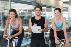 Fit women in a spin class with trainer smiling at camera Stock Images