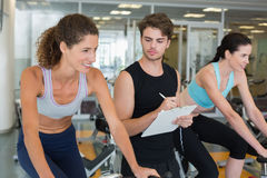 Fit women in a spin class with trainer taking notes Stock Images