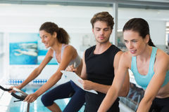 Fit women in a spin class with trainer taking notes Royalty Free Stock Photography