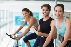 Fit women in a spin class with trainer taking notes and smiling at camera. At the gym Royalty Free Stock Photography
