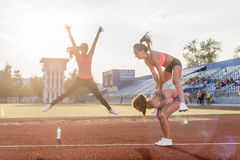 Fit women at the stadium playing leap frog. Royalty Free Stock Photography