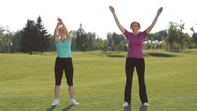 Fit women stretching hands and warming up in park stock footage