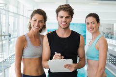 Fit women with trainer taking notes and smiling at camera. At the gym Stock Photos