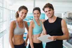 Fit women with trainer taking notes and smiling at camera. At the gym Royalty Free Stock Images