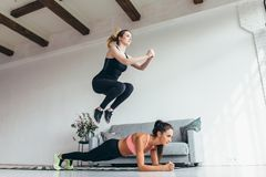 Fit women training home. Girl jumping over her friend while woman performing plank position. Fit women training home. Girl jumping over her friend while women Royalty Free Stock Photography
