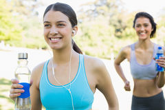 Fit women with water bottle jogging Royalty Free Stock Photos