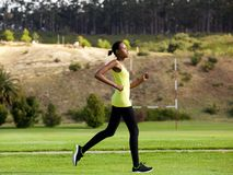 Fit young african american woman jogging outdoors in a park Stock Photography