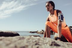 Runner doing stretching workout at rocky beach. Fit young african female runner doing stretching workout. Fitness woman exercising at rocky beach after a run stock photo