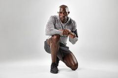 Fit young african man kneeling on grey background Stock Photos