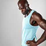 Fit young african man with muscular build. Looking down over grey background Royalty Free Stock Image