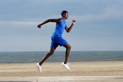 Fit young african man running along the beach Royalty Free Stock Images