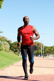 Fit young african man running outdoors at the park Royalty Free Stock Images