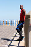 Fit young african man standing at seaside promenade. Full length portrait of fit young african man standing at seaside promenade Royalty Free Stock Photos