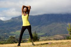 Fit young african woman doing stretching workout Stock Photo