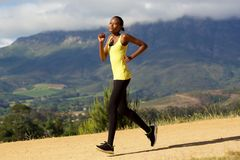Fit young african woman jogging outdoors in nature Stock Image