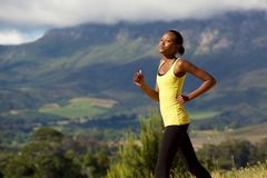 Fit young african woman running outdoors in nature Royalty Free Stock Images