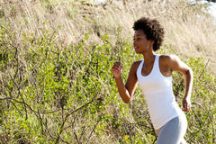Fit young african woman running outdoors Stock Photos