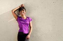 Fit young african woman standing and resting outdoors after running exercise session. Portrait of fit young african woman standing and resting outdoors after Stock Photo