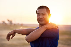 Fit young Asian man stretching his arms before a run. Portrait of an athletic young Asian man stretching his arms before going for a solo run outside on a sunny Royalty Free Stock Image