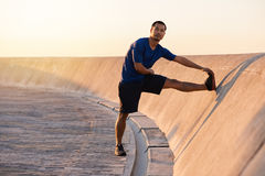 Fit young Asian man stretching his legs before a run Royalty Free Stock Photography