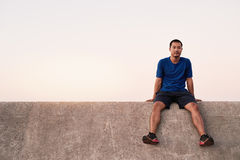 Fit young Asian man taking a break from a run Royalty Free Stock Photos