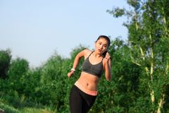 Fit young asian woman jogging at park Royalty Free Stock Image
