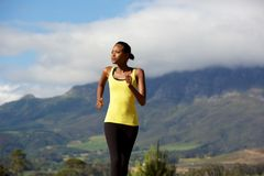 Fit young black woman running in nature Stock Images