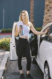 Fit Young Blonde Girl Stands at Her Car with Water Bottile in Her Hand After a Workout royalty free stock photo