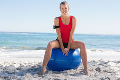 Fit young blonde sitting on exercise ball smiling at camera Stock Images