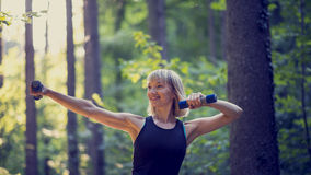 Fit young blonde woman working out with dumbbells outside Royalty Free Stock Images