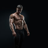 Fit young bodybuilder posing over black background Stock Photo