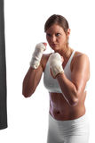Fit young caucasian woman punching the bag Royalty Free Stock Image