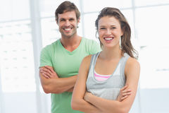 Fit young couple with arms crossed in exercise room Stock Photography
