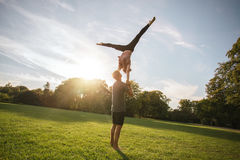 Fit young couple doing acro yoga in park Royalty Free Stock Images