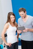 Fit young couple at a gym looking at a tablet-pc Royalty Free Stock Photography