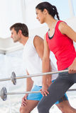 Fit young couple holding barbells in the gym Royalty Free Stock Photography