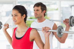 Fit young couple lifting barbells in gym Stock Image