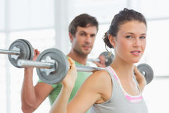 Fit young couple lifting barbells in gym Royalty Free Stock Image