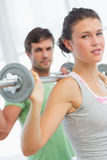 Fit young couple lifting barbells in gym Stock Photos