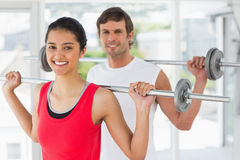 Fit young couple lifting barbells in gym Stock Images
