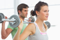Fit young couple lifting barbells Stock Images