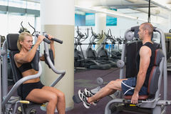 Fit young couple using fitness machines at gym Royalty Free Stock Photography
