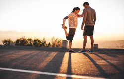 Fit young couple warming up before a run together Royalty Free Stock Photo