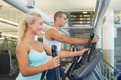 Fit young couple working on x-trainers at gym. Side view of a fit young couple working on x-trainers at the gym royalty free stock photo