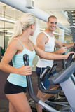 Fit young couple working on x-trainers at gym Royalty Free Stock Images