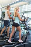 Fit young couple working on x-trainers at gym Royalty Free Stock Photos