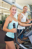 Fit young couple working on x-trainers at gym Stock Images